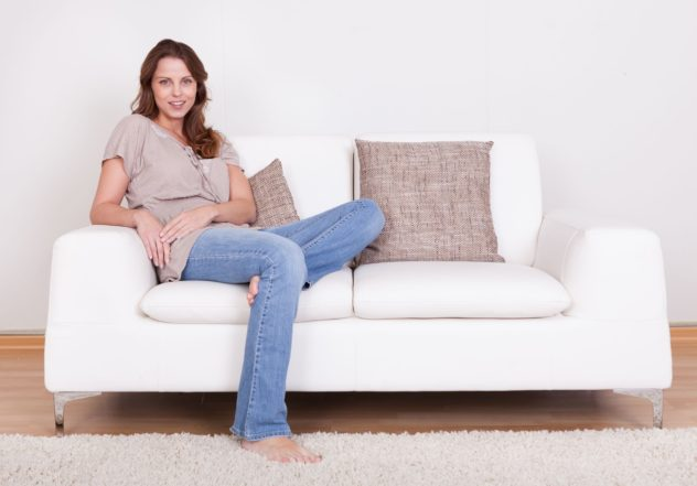 Woman sitting on white couch in jeans